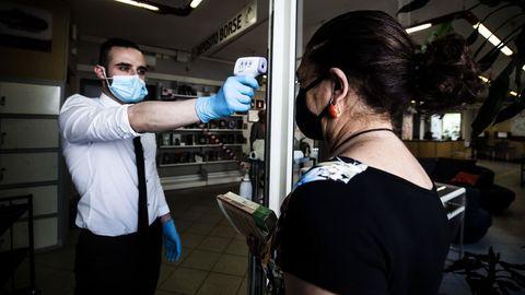 Un empleado de una librería romana toma la temperatura a una clienta antes de acceder al establecimiento