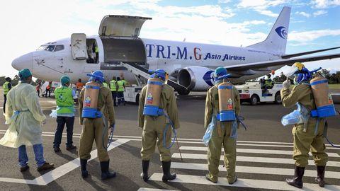 Trabajadores de Timor Oriental se preparan para descargar la ayuda médica que llega en un avión procedente de China