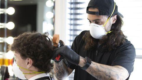 El barbero Niko Deniro, ayer, con guantes y una mascarilla, cortandl el pelo en su negocio de Kasino, en Burlington, Massachusetts