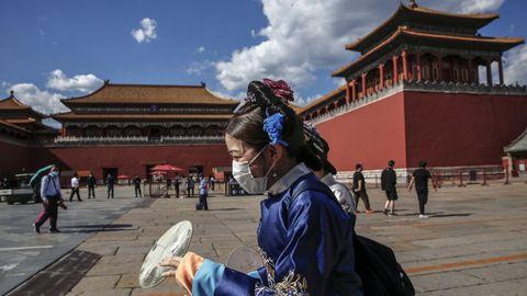 Una mujer vestida con el traje tradicional camina ante la Ciudad Prohibida de Pekín