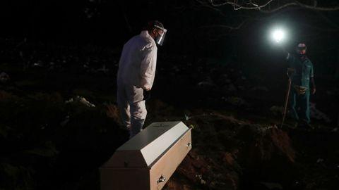 Un sepulturero se prepara para enterrar el cuerpo de una fallecida por covid-19