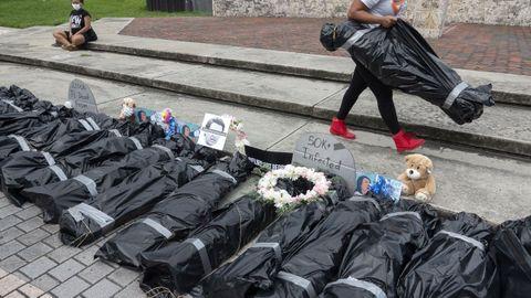 Un activista porta en Miami bolsas que simulan cuerpos de fallecidos por covid-19 en un acto de protesta