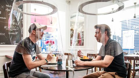 El diseñador Christophe Gernigon (derecha) prueba en un restaurante de París una burbuja de protección creada para prevenir contagios