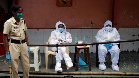 Trabajadores sanitarios aguardan cerca de un templo para realizar test de covid-19