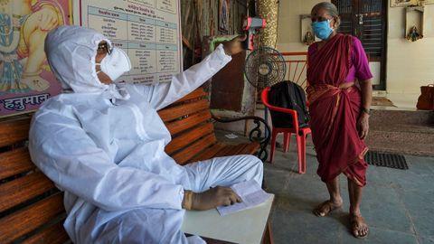Un sanitario en Bombai toma la temperatura a una mujer