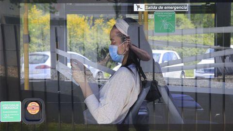 Una joven con mascarilla en el bus urbano de Lugo