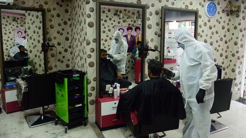 Un peluquero protegido contra el contagio, el sábado en su negocio de Kolkata, India