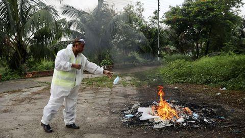 En Daca, la capital de Bangladesh, un trabajador quema su traje de protección tras asistir al entierro de un fallecido por coronavirus