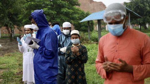 Familiares oran durante el entierro de un fallecido por covid-19 en Bangladesh