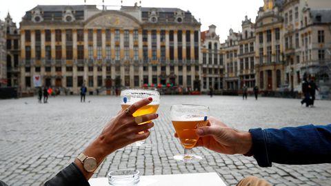 En Bélgica han reabierto bares y restaurantes. Una pareja brinda en la Gran Plaza de Bruselas