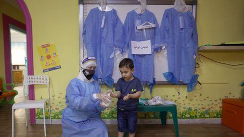 En Jordania, una profesora enseña a un alumno cómo utilizar los productos desinfectantes