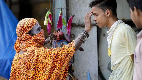 En Calcuta, un monje con máscara facial bendice a un joven