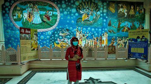 Una mujer con mascarilla visita un templo en India