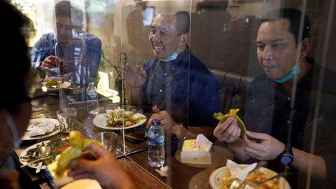 Las mamparas plásticas separadoras se han convertido en habituales en los restaurantes de Jakarta