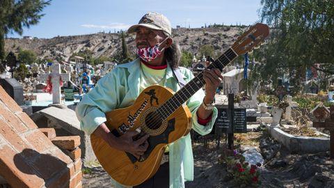 Un hombre con mascarilla toca la guitarra en un cementerio mexicano