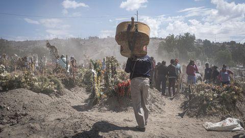 Un músico lleva su instrumento a un cementerio mexicano en el que están enterrando a fallecidos por coronavirus