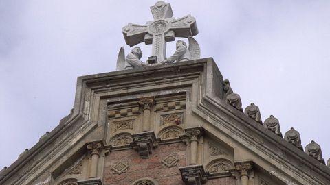 En la imagen se aprecia el lugar donde está el obús, bajo el ángel derecho del remate de la iglesia de San Juan el Real de Oviedo