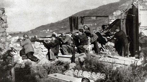 Voluntarios y guardias civiles defienden la posición de San Pedro de los Arcos de Oviedo durante la Guerra Civil. El cementerio, desde donde disparan, quedó parcialmente destruido durante los combates