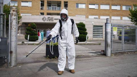 Un operario desinfecta la entrada del hospital de Verín