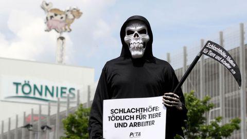Un activista protesta ante las instalaciones de la cárnica afectada por el brote en Alemania