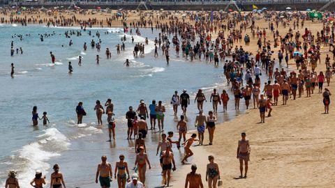 Varias personas disfrutan de un soleado día de verano en la playa de San Lorenzo en Gijón,