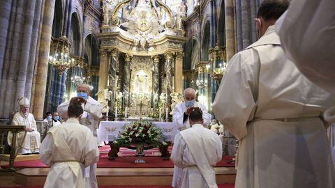 El obispo en primer lugar, y luego el resto de sacerdotes, imponen las manos sobre los candidatos.