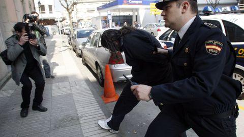 Momento en que uno de los detenidos entra en el juzgado custodiado por la policía el 24 de marzo del 2009