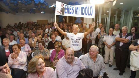 Toñito sostiene una pancarta durante un mitin de Feijoo en Carballo, en el 2012