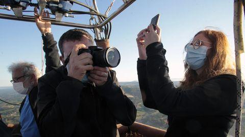Dos viajeros fotografían el paisaje de la zona del Miño desde el globo