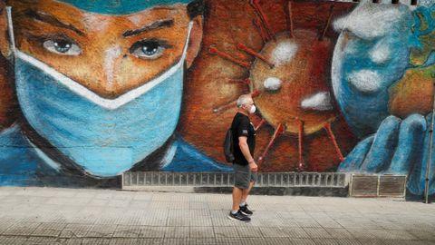 Un hombre camina junto a un mural de homenaje a los sanitarios en Melide