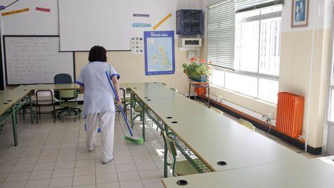 Personal de limpieza trabajando en un aula de un colegio público en una foto de archivo
