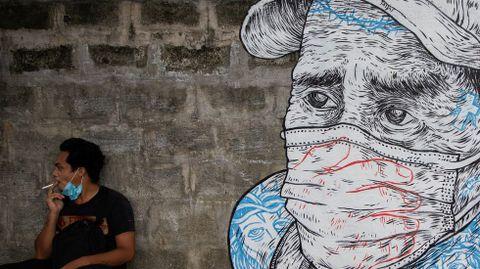 Un hombre fuma cerca de un mural sobre el coronavirus en Manila, Filipinas