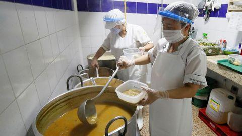 Trabajadores preparan alimentos para repartir dada la crisis derivada de la pandemia Covid-19, en un comedor comunitario de Bogotá, Colombia