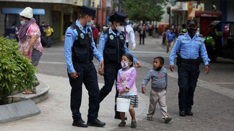Policías hondureños hablan con dos niños mientras brindan seguridad en el Parque Central este miércoles, en Tegucigalpa, Honduras