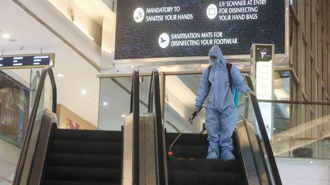 Un hombre en equipo de protección personal rocía desinfectante en una escalera mecánica dentro de un centro comercial para desinfectarlo antes de que vuelvan a abrir en Mumbai, India