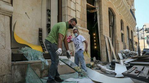 Trabajadores recogiendo cristales rotos de una tienda tras la explosión