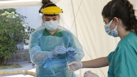 Personal sanitario en la carpa para realizar las pruebas PCR a personas desde su coche, instalada en la entrada de urgencias del hospital Gil Casares