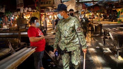 Un policía armado patrulla un mercado público en TayTay, Filipinas
