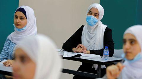 Estudiantes palestinos escuchan a su profesor mientras un nuevo año escolar empieza parcialmente entre la preocupación por la propagación del coronavirus