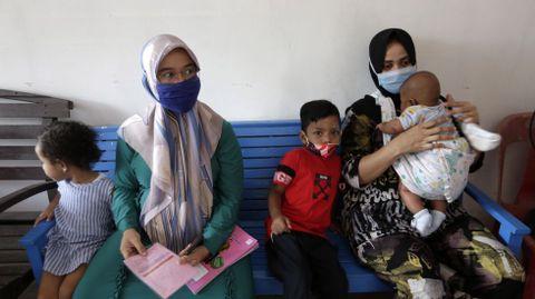 Unas madres y sus hijos esperan durante la campaña rutinaria de inmunización en Banda Aceh, Indonesia