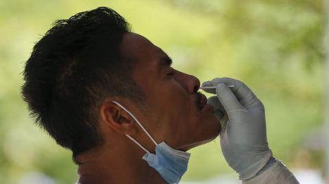 Un sanitario le toma una muestra de saliva a un jugador de fútbol en Yangon, Myanmar