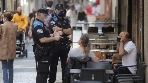 Dos agentes de la policía local de A Coruña patrullan por una céntrica calle de la ciudad. Imagen de archivo