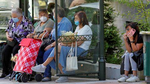 Una mujer fuma junto a la parada de un autobú, en el centro de Oviedo, mientras en la marquesina un grupo de ususarias se protege con mascarillas.