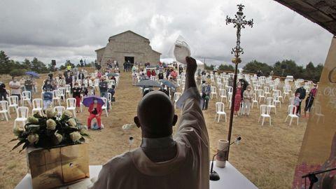 Momento en que el párroco Xabier Díaz levanta una mascarilla hacia los fieles en la misa de la una