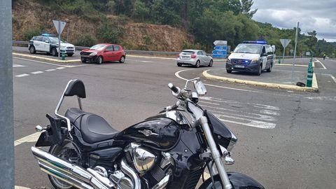 La moto en la que iban los heridos y, al fondo, el vehículo que impactó contra ella