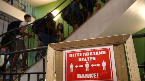 Un letrero exhorta a guardar las distancias en una escuela recién abierta de Hanau, en Alemania