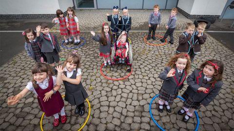Escolares de Glasgow, agrupados por parejas al ser hermanos, en el primer día de clase