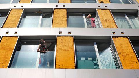 Dos okupas hablan entre ellos desde las ventanas de un edificio tomado en Vigo y que fue desalojado por la Policía