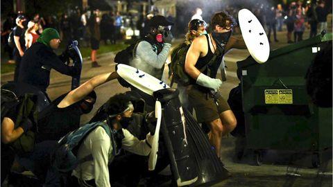 Manifestantes se protegen con escudos caseros de las balas de goma y gases lanzados por la policía en Kenosha