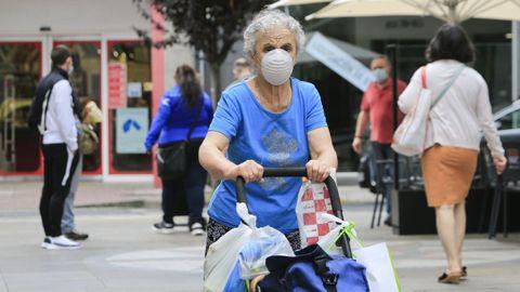 Una mujer de compras en el barrio de A Milagrosa, uno de los más populosos de Lugo y que está sometido a restricciones por la transmisión del coronavirus